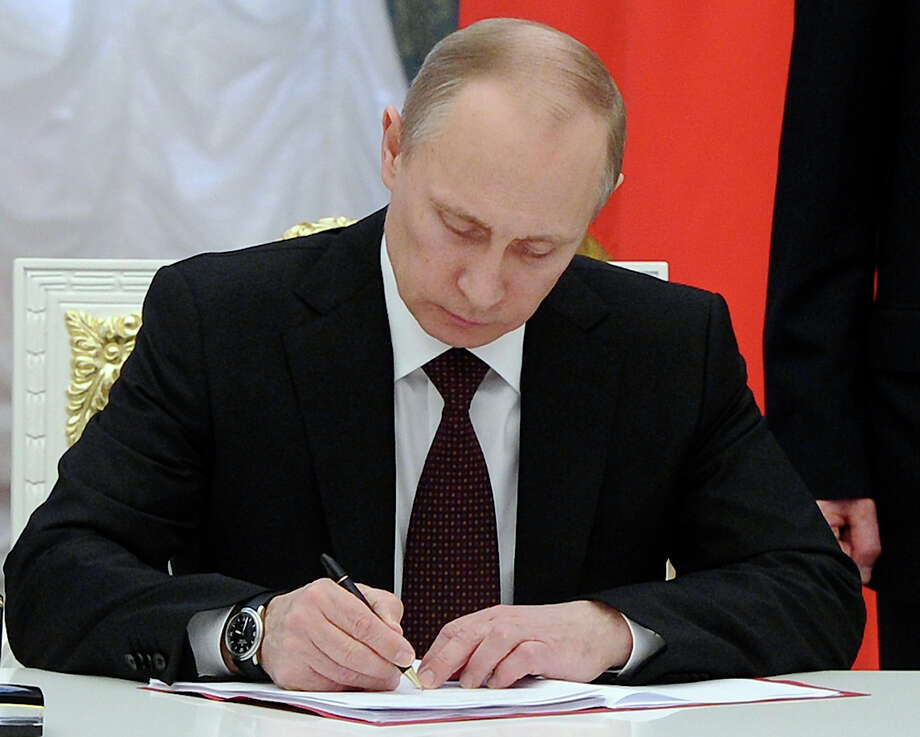 Russian President Vladimir Putin signs bills making Crimea part of Russia in the Kremlin in Moscow, Friday, March 21, 2014. President Vladimir Putin completed the annexation of Crimea on Friday, signing the peninsula into Russia at nearly the same time his Ukrainian counterpart sealed a deal pulling his country closer into Europe's orbit. (AP Photo/RIA-Novosti, Mikhail Klimentyev, Presidential Press Service) ORG XMIT: MOSB108 Photo: Mikhail Klimentyev / RIA Novosti Kremlin