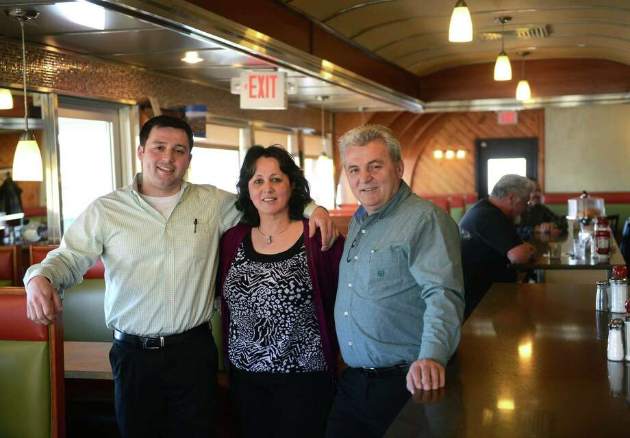 George Psarofagis, left, and his parents Maria and Bill Psarofagis, pose inside the New Holiday Diner in Danbury, Conn. Thursday, March 6, 2014.  The diner, owned and operated by the Psarofagis family, is open every day for breakfast, lunch and dinner. Photo: Tyler Sizemore / The News-Times
