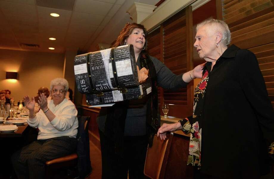 Choir director Connie Swanson, center, gives a gift to Elinor Cavallo James at the surprise retirement party for longtime teacher Cavallo James at Jim Barbarie's Restaurant in Danbury, Conn. Friday, March 21, 2014.  Cavallo James retired in December at the age of 88 after teaching Spanish for 28 years at Broadview Middle School.  Dozens of her colleagues, friends and family members gathered to celebrate her time as a teacher. Photo: Tyler Sizemore / The News-Times