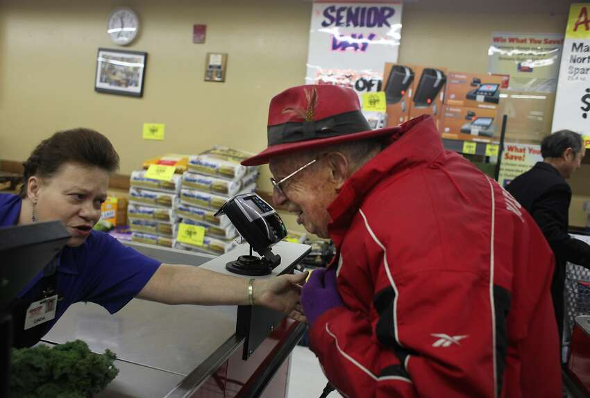 Cashier Linda Hutchinson greets Allen Stross as he stands in the checkout line while shopping at Grocery Outlet in Berkeley on Senior Day.