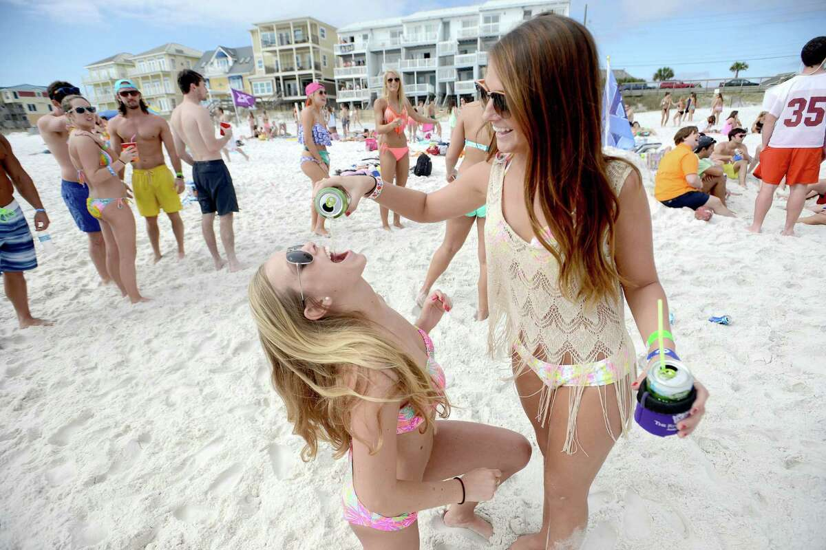University of Tennessee spring breakers Bree Thomas, right, pours a beer into the mouth of Rachael Dubois on Tuesday March 18, 2014 in Destin, Fla.