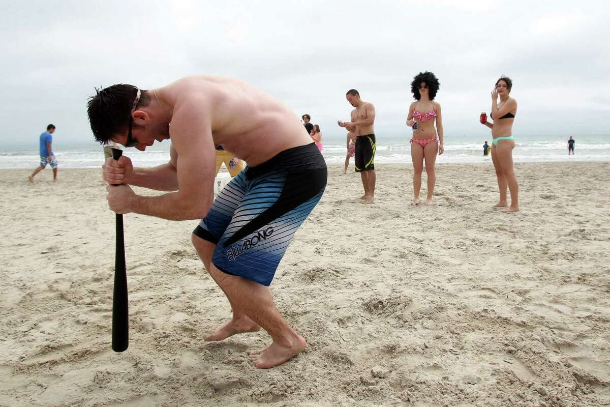 Adam Wruck, a senior at Texas A&M University-College Station, spins around on a baseball bat before hitting a pitch Tuesday, March 11, 2014 during spring break on the beach in Port Aransas, Texas. Sun and warmer weather brought out bigger crowds at beaches across the Coastal Bend.