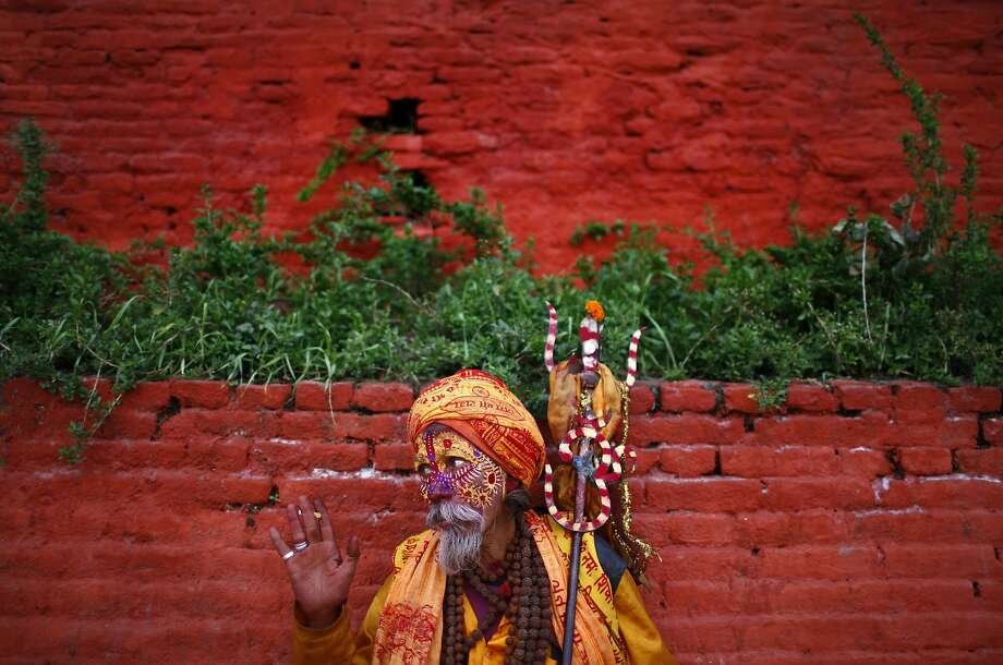 Your generosity is appreciated: A face-painting sadhu (Hindu holy man) looking for alms waves to the tourists at the Pashupatinath  