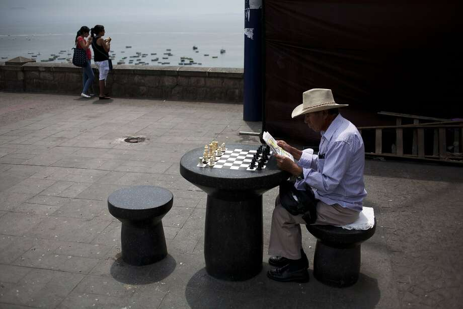 Chess teacher Miguel Barreneche Pena catches up on current events while waiting for a game in Lima. Barreneche Pena charges customers one Peruvian sol, or 36 cents, for the pleasure of losing to him. Photo: Rodrigo Abd, Associated Press