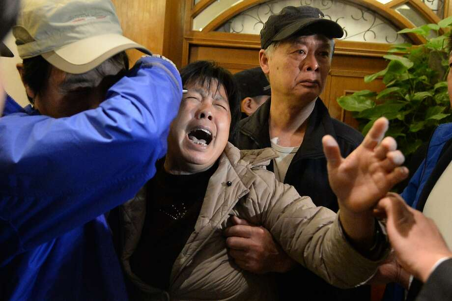 A passenger's relative cries in Beijing after hearing the Malaysian prime minister announce that the missing plane had crashed into the Indian Ocean. Photo: Goh Chai Hin, AFP/Getty Images