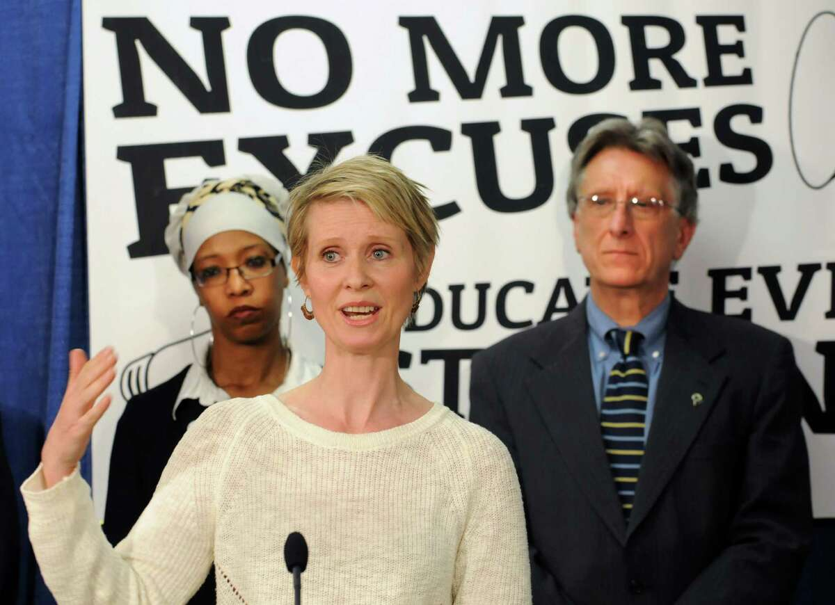 Actress and education advocate Cynthia Nixon speaks during a press conference with school superintendents, academics and other officials to push for more funding for schools Monday, March 24, 2014, at the Legislative Office Building in Albany, N.Y. Advocacy Director for the Alliance for Quality Education Zakiyah Ansari, left, and Fairport Central School District Superintendent William Cala stand in background. (Lori Van Buren / Times Union)