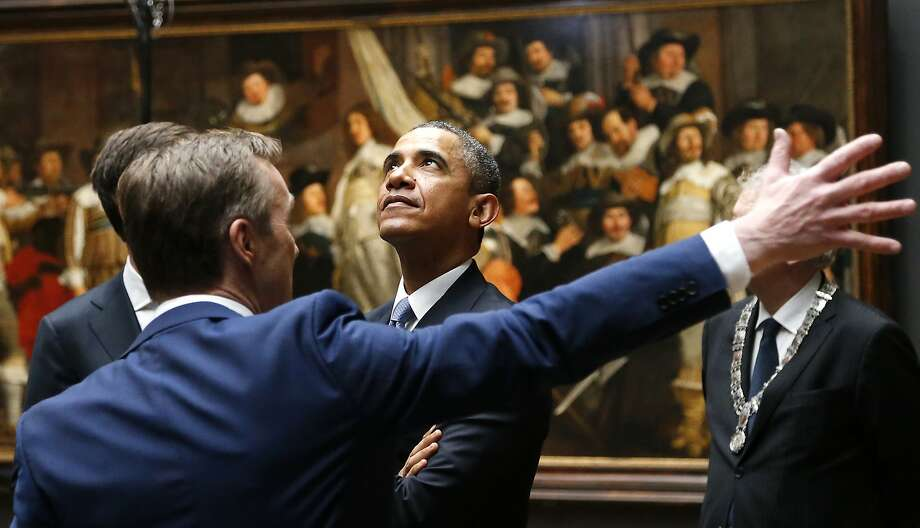 U.S. President Barack Obama, center, listens to Rijksmuseum director Wim Pijbes, seen from the back, in front of  Dutch master Rembrandt's The Night Watch painting during a visit to the Rijksmuseum in Amsterdam, Netherlands, Monday, March 24, 2014. Obama will attend the two-day Nuclear Security Summit in The Hague. (AP Photo/Frank Augstein) Photo: Frank Augstein, Associated Press