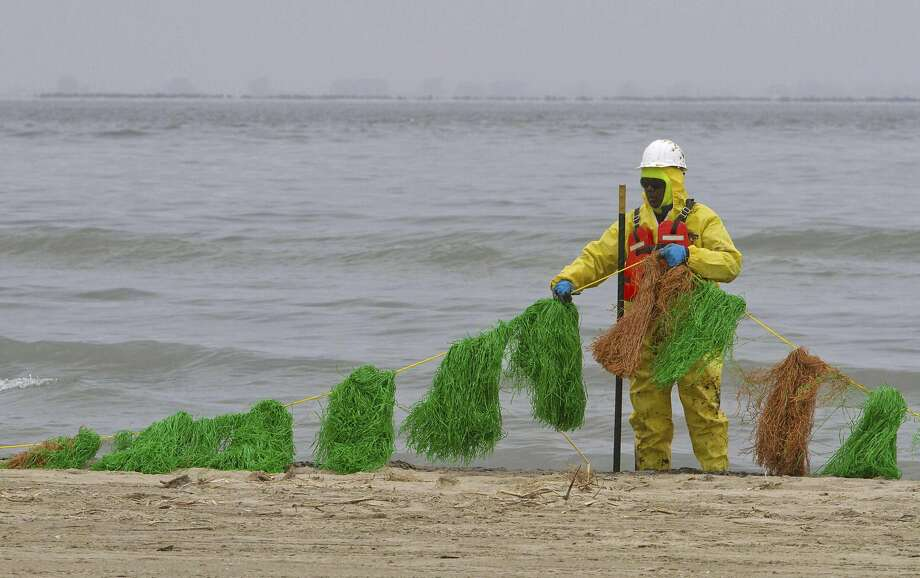 A worker places oil absorbent snares on the beach on the east end of Galveston Island March 24, 2014. U.S. authorities prepared to partially re-open the Houston Ship Channel on Monday afternoon after an oil barge spill shut it for a third day, forcing the nation's second-largest refinery to curb production. REUTERS/Richard Carson (UNITED STATES - Tags: DISASTER ENERGY ENVIRONMENT) Photo: Richard Carson, Reuters