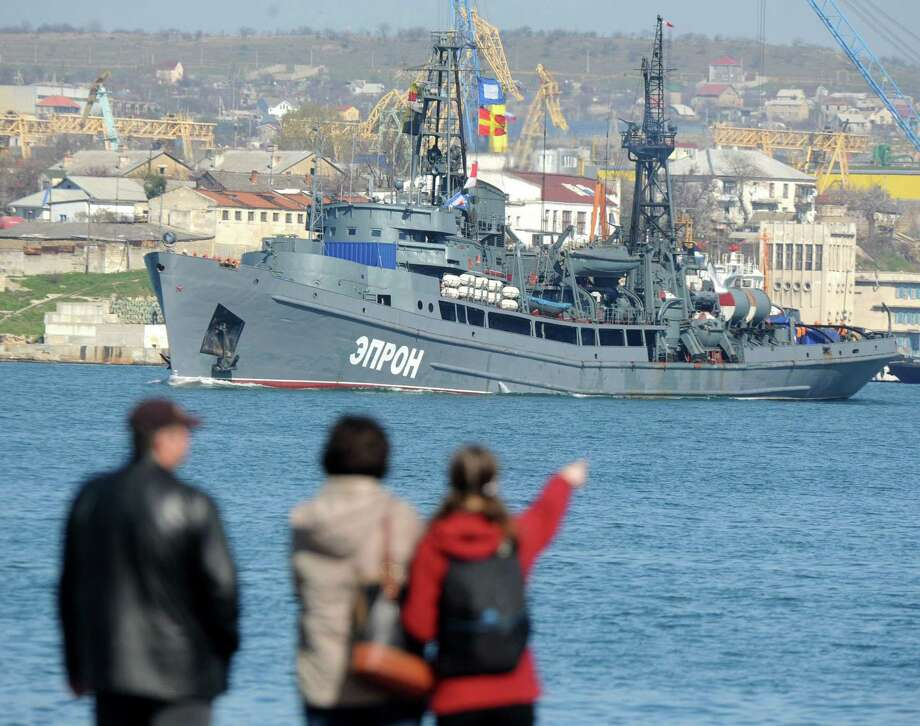 People look at a Russian military ship sailing in the bay of the Crimean city of Sevastopol.  Crimea's rebel leader urged Russians across Ukraine to rise up against Kiev's rule.  Photo: Viktor Drachev / AFP / Getty Images / AFP