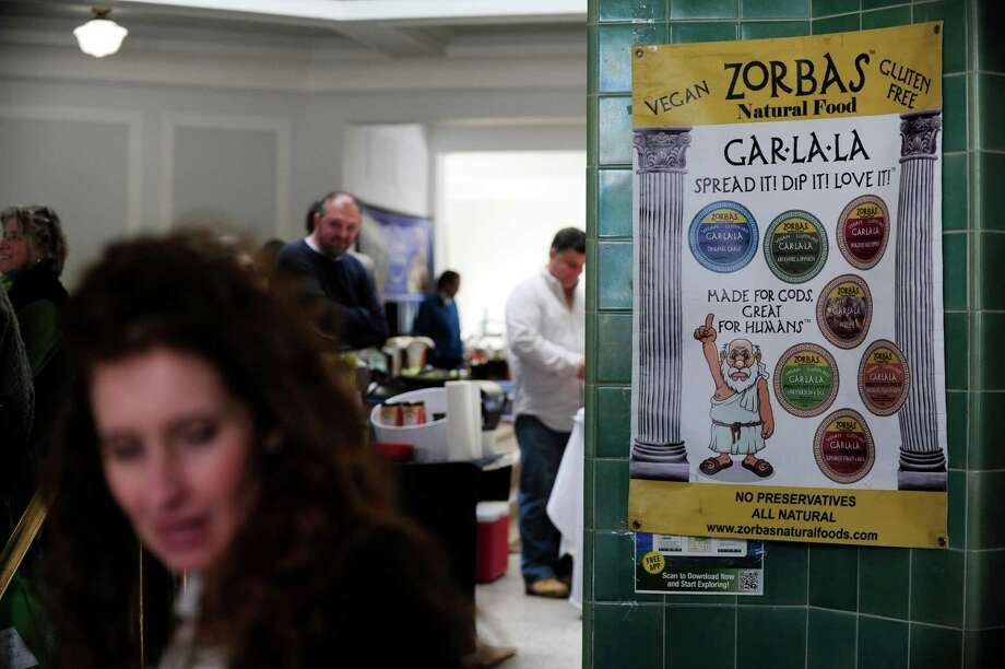Colleen Zorbas, foreground left, works at her family business, Zorbas Natural Foods, booth at the Spa City Farmers' Market on Sunday, March 23, 2014, in Saratoga Springs, N.Y.  (Paul Buckowski / Times Union) Photo: Paul Buckowski / 00026212A
