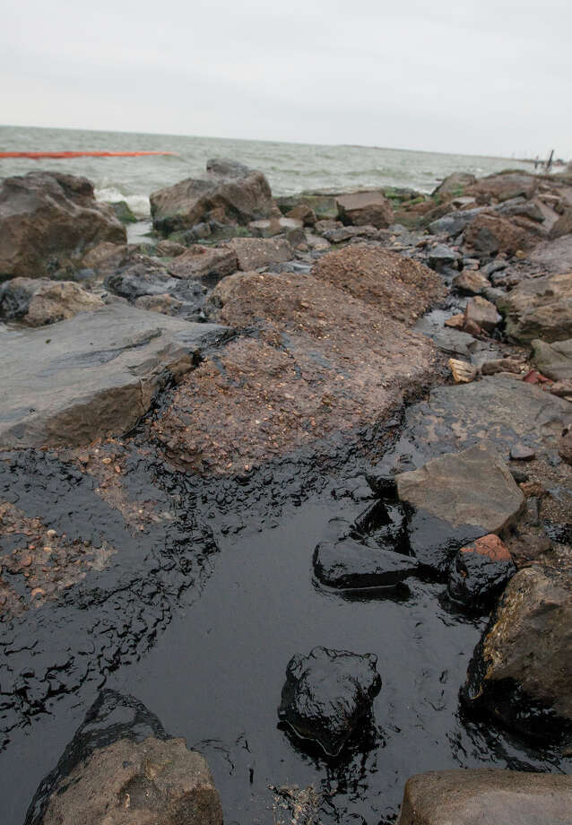 Oil sits on rocks along the shore area along Boddeker Rd. on the Eastern end of Galveston, Monday, March 24, 2014, in Galveston. The oil washed ashore after a barge carrying heavy oil collided with a ship Saturday in the busy Houston Ship Channel. Photo: Cody Duty, Houston Chronicle / © 2014 Houston Chronicle