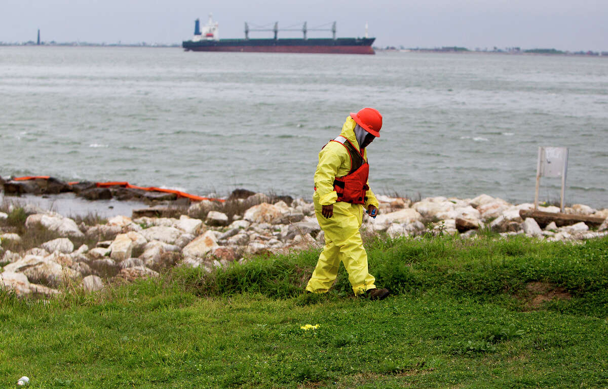 Crews work to clean oil from the shore area along Boddeker Rd. on the Eastern end of Galveston, Monday, March 24, 2014, in Galveston. The oil washed ashore after a barge carrying heavy oil collided with a ship Saturday in the busy Houston Ship Channel.