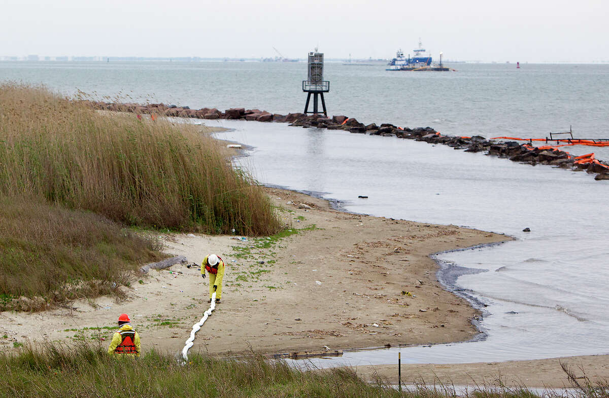 Crews work to clean oil from the shore area along Boddeker Rd. on the Eastern end of Galveston, Monday, March 24, 2014, in Galveston. The oil washed ashore after a barge carrying heavy oil collided with a ship in the busy Houston Ship Channel.