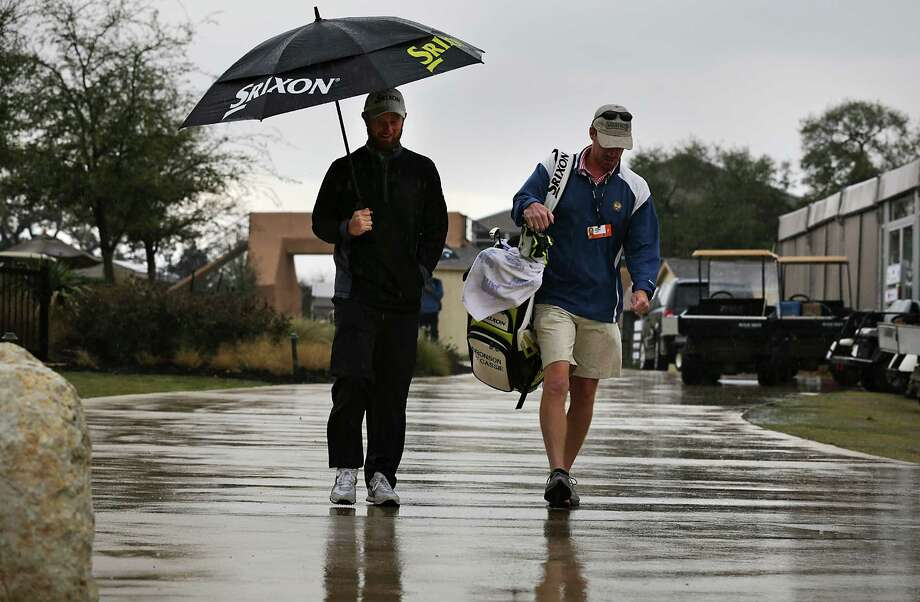 Bronson La'Cassie, left, and his caddie David DuBord, leave the course as a thunderstorm halted play at The Bay Ltd. Pro-Am at the 2014 Valero Texas Open on the TPC San Antonio AT&T Oaks Course. Monday, March 24, 2014. Photo: Bob Owen, San Antonio Express-News / ©2013 San Antonio Express-News