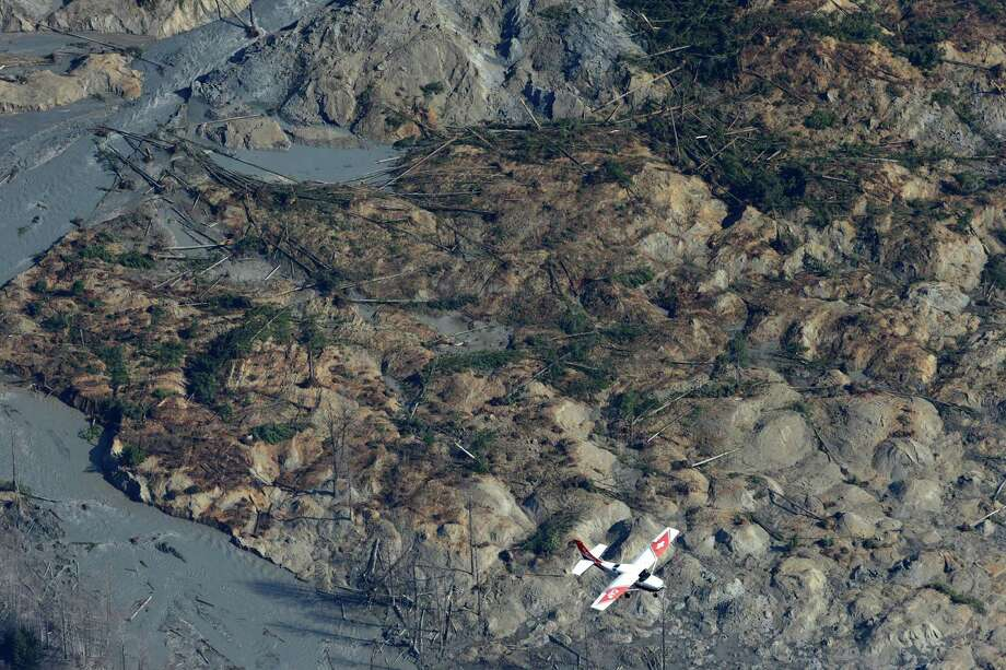 A Civil Air Patrol plane flies over the massive mudslide. Photo: Ted S. Warren, Associated Press / AP
