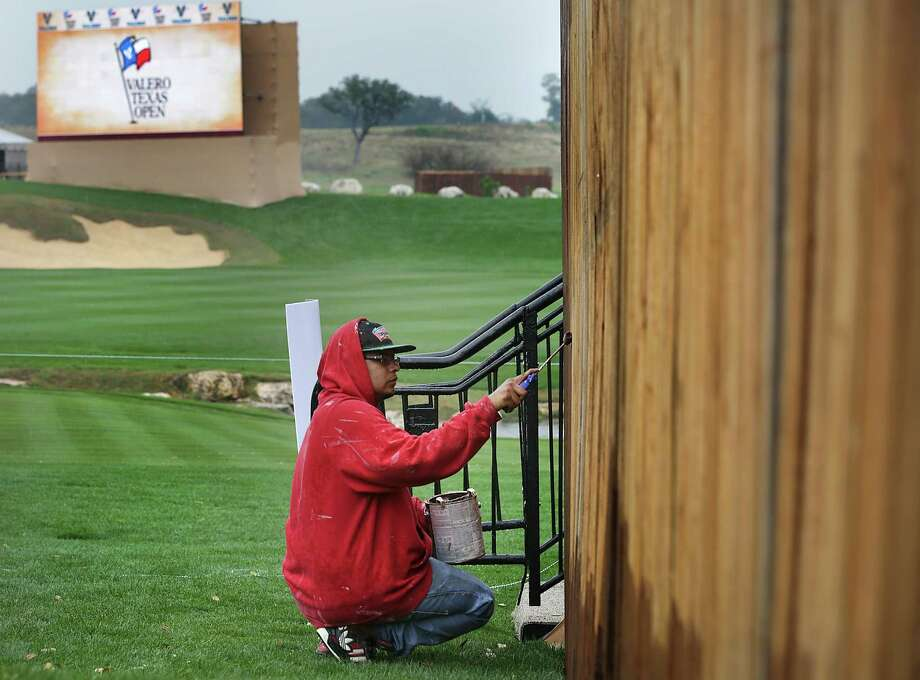 David Hernandez of Parra Painting and Decorating, puts a final coat of paint on fencing, in the rain, as a thunderstorm halted play at The Bay Ltd. Pro-Am at the 2014 Valero Texas Open on the TPC San Antonio AT&T Oaks Course. Monday, March 24, 2014. Photo: Bob Owen, San Antonio Express-News / ©2013 San Antonio Express-News