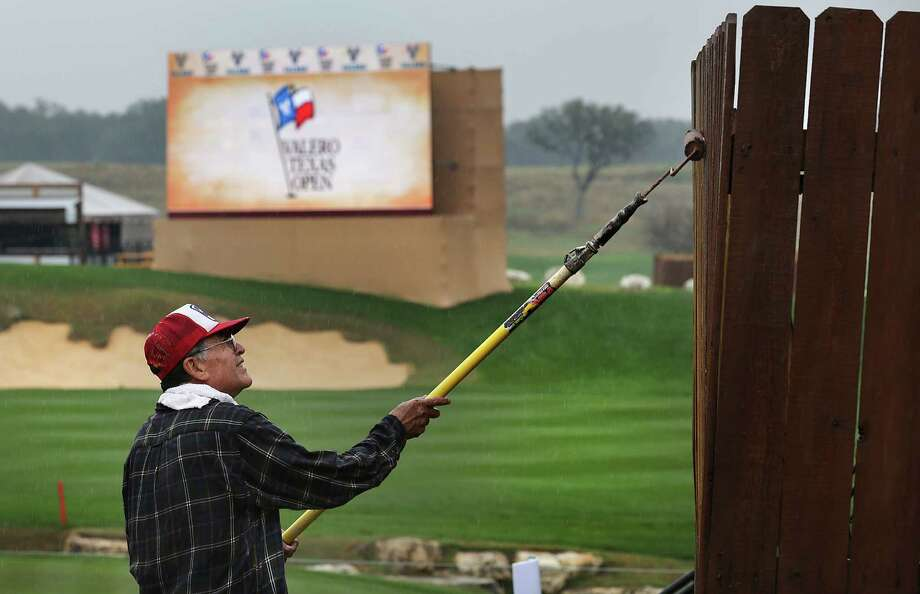 Julian Parra of Parra Painting and Decorating, puts a final coat of paint on fencing, in the rain, as a thunderstorm halted play at The Bay Ltd. Pro-Am at the 2014 Valero Texas Open on the TPC San Antonio AT&T Oaks Course. Monday, March 24, 2014. Photo: Bob Owen, San Antonio Express-News / ©2013 San Antonio Express-News