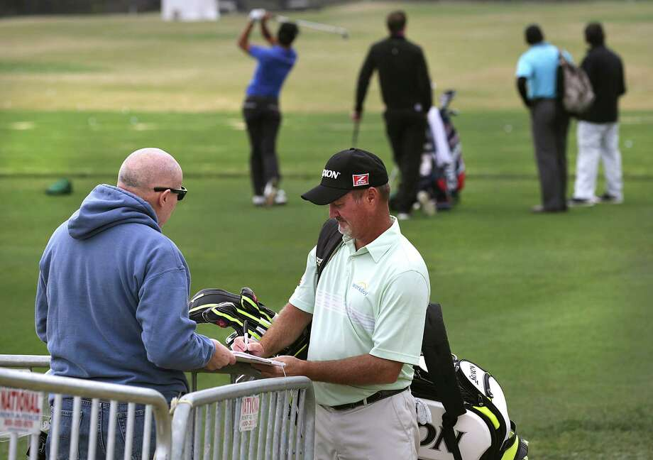 Jerry Kelly, right, signs an autograph for Bill Sheehan of Chicago as players practice on the driving range at the 2014 Valero Texas Open on the TPC San Antonio AT&T Oaks Course. Monday, March 24, 2014. Photo: Bob Owen, San Antonio Express-News / ©2013 San Antonio Express-News
