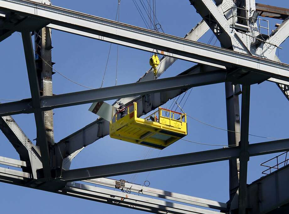 Workers retrieve a piece of metal on the cantilever section of the Bay Bridge's eastern span. Removing parts from both sides of the section simultaneously is expected to decrease the demolition time of the old span. Photo: Brant Ward, The Chronicle