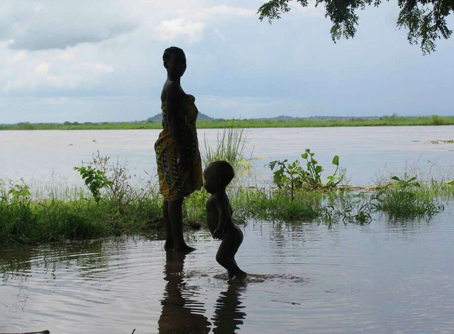 FILE - In this Jan. 9, 2008, file photo provided by UNICEF a woman and child wade in flood waters in Mutarara, Mozambique in the Tete district.  Thousands of people who lost their homes in floods last year are at risk again as the rising Zambezi river waters threaten their resettlement camps. Top climate scientists are gathering in Japan to finish up a report on the impact of global warming. And they say if you think climate change is only faced by some far-off polar bear decades from now, well, you're mistaken. They say the dangers of a warming Earth are immediate and human.  (AP Photo/Theirry Delvigne-Jean UNICEF) Photo: THIERRY DELVIGNE-JEAN, HOEP / UNICEF