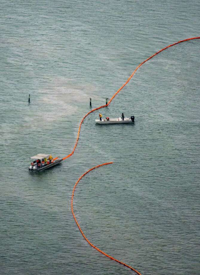 Crews place protective boom along the seashore near Port Bolivar after the oil spill. The incident might cause seafood prices to rise at restaurants and some retailers. Photo: Smiley N. Pool / Houston Chronicle / Houston Chronicle