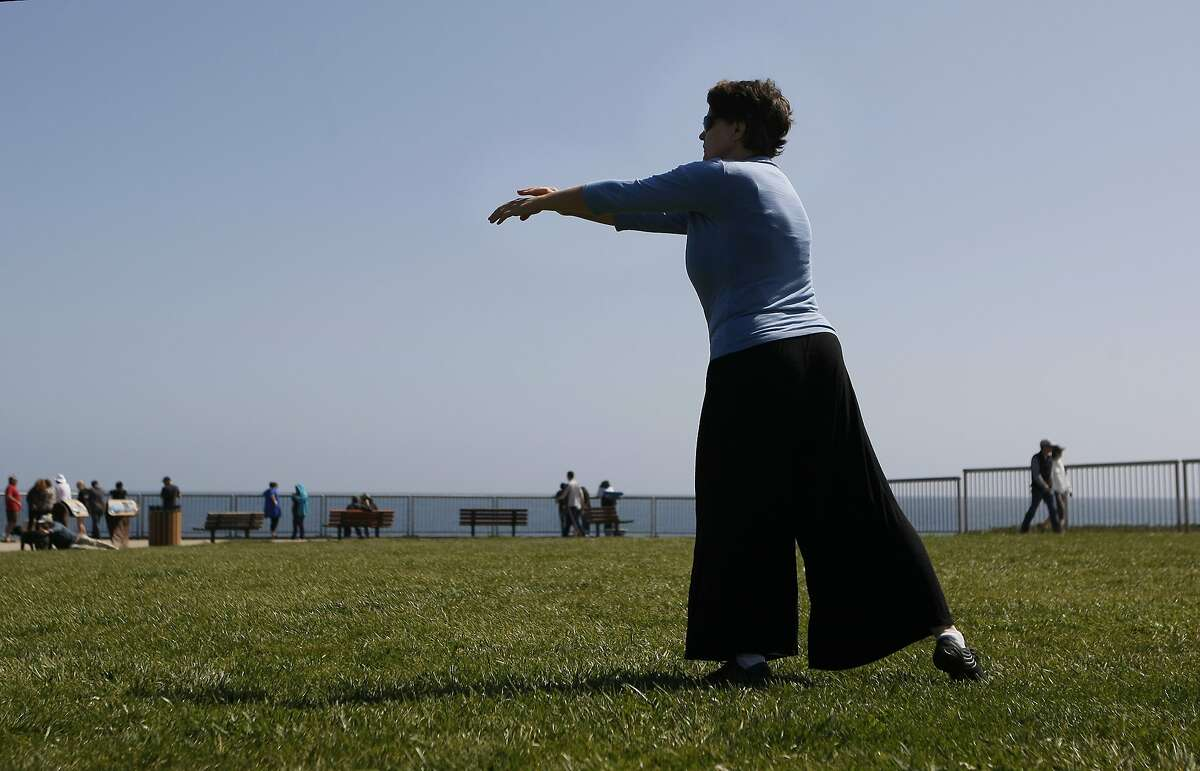 Lisa Geiszler, 47, does qigong, a form a tai chi, next to Lighthouse Field State Beach on March 22, 2014 in Santa Cruz, Calif. Geiszler used to be a very active woman, once biking from Vancouver to Los Angeles, but she was bedridden due to chronic fatigue immune deficiency syndrome for many years.