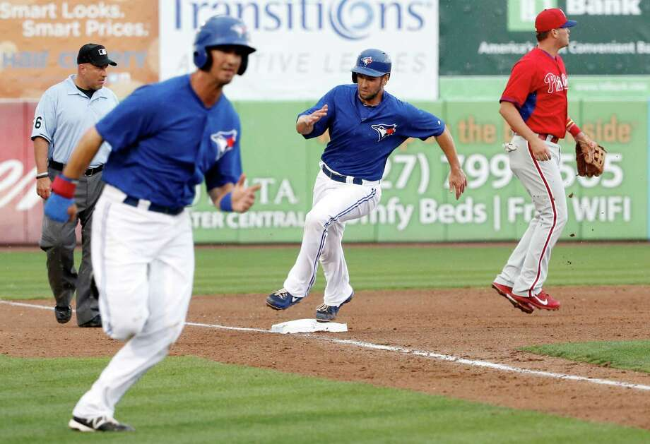 Third base umpire Eric Cooper, left, watches as Toronto Blue Jays Gabe Jacobo, second from left, runs home and Josh Thole, second from right, rounds third on teammate Brett Carroll's seventh-inning two-run double as Philadelphia Phillies third baseman Reid Brignac, right, waits for a throw in a spring exhibition baseball game in Dunedin, Fla., Monday, March 24, 2014. Carroll was out at third. (AP Photo/Kathy Willens) ORG XMIT: FLKW118 Photo: Kathy Willens / AP