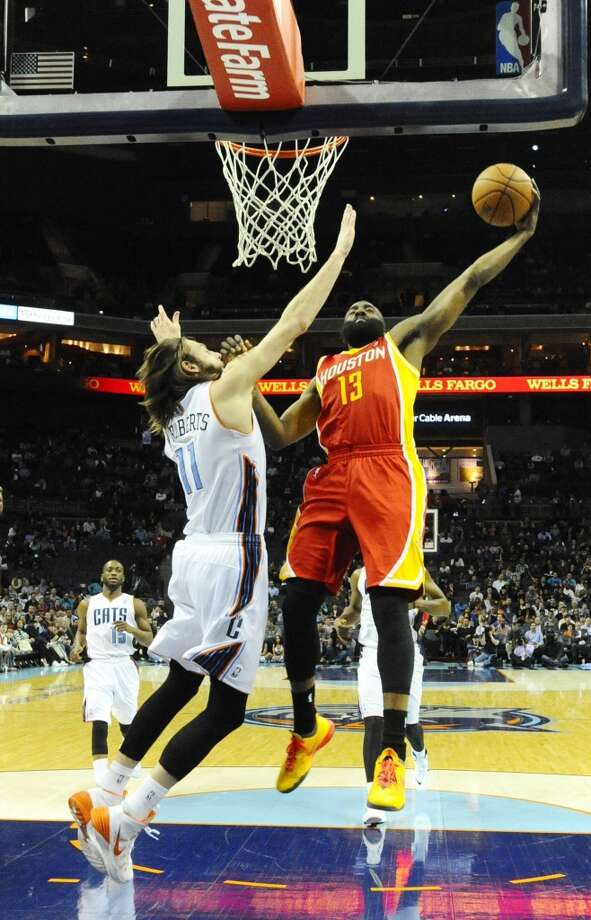 Rockets shooting guard James Harden dunks over Josh McRoberts of the Bobcats. Photo: David T. Foster III, Charlotte Observer/MCT