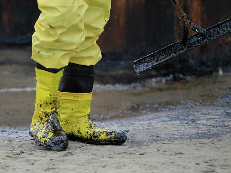 Oil on the boots of a worker is testament to the work needed to reverse the effects of the spill. Photo: Karen Warren, Staff / © 2014 Houston Chronicle
