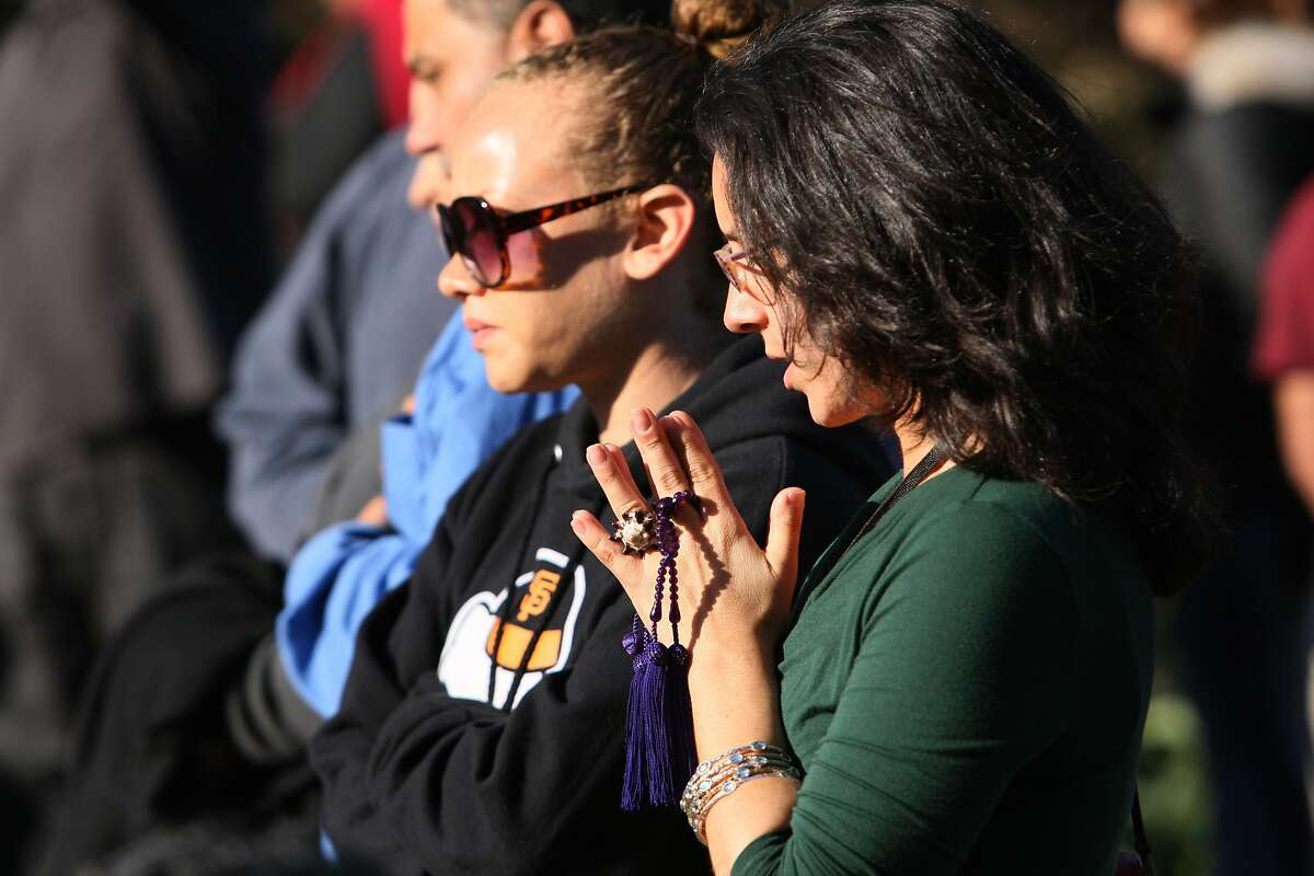 A woman clasps her hands together in mourning at a vigil held for Alejandro Nieto, a man fatally shot by police last Friday evening in Bernal Heights Park, in San Francisco, Calif. on March 24, 2014.