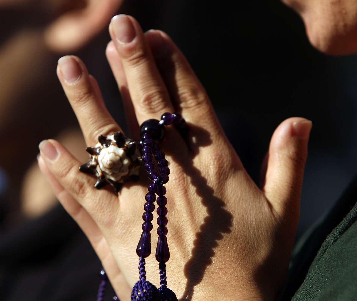 A young woman clasps her hands with buddhist prayer beads as family and friends of Alejandro Nieto gathered on Bernal Heights Park in San Francisco, Calif., on Monday, March 24, 2014. Nieto was fatally shot by San Francisco police officers Friday evening at Bernal Heights Park.