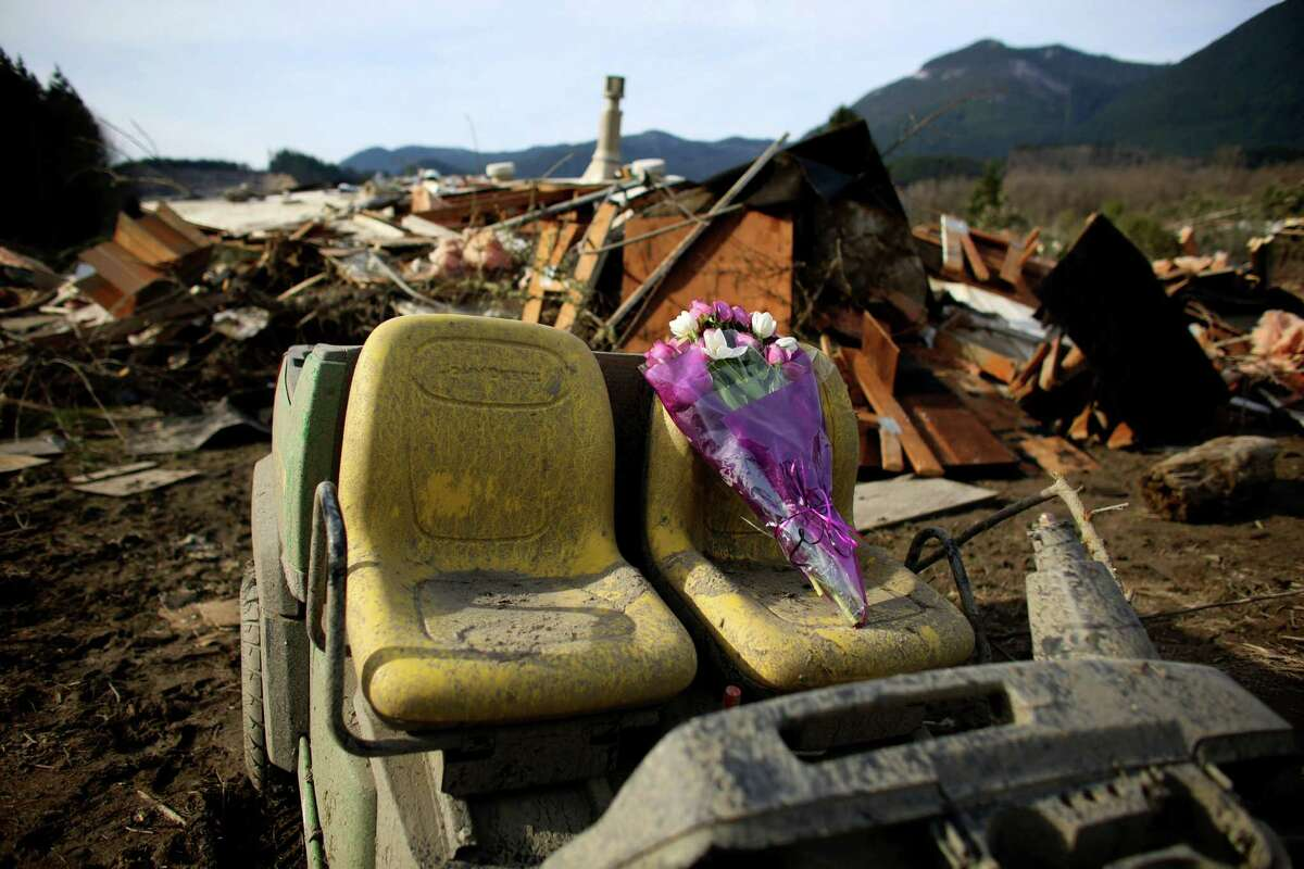 A bouquet of flowers left for the deceased sits perched on the seat of a damaged vehicle in the wreckage of homes and lives destroyed by a mudslide near Oso, Wash. In the wake of Saturday's mudslide on Highway 530 in Snohomish County, there have been over 100 reports of missing people and the death toll has risen to 14.