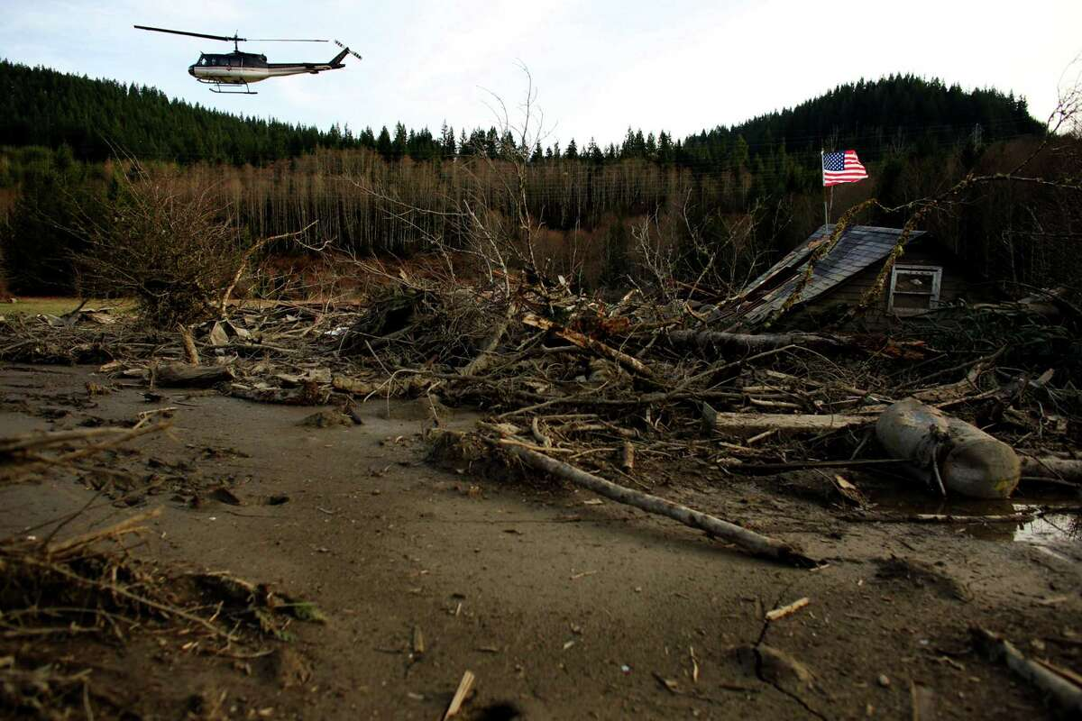 A rescue helicopter flies over the wreckage of homes and lives destroyed by a mudslide near Oso, Wash.