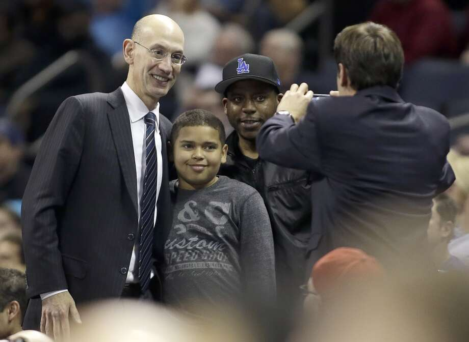 NBA commissioner Adam Silver poses with fans at the Rockets game against the Bobcats. Photo: Bob Leverone, Associated Press