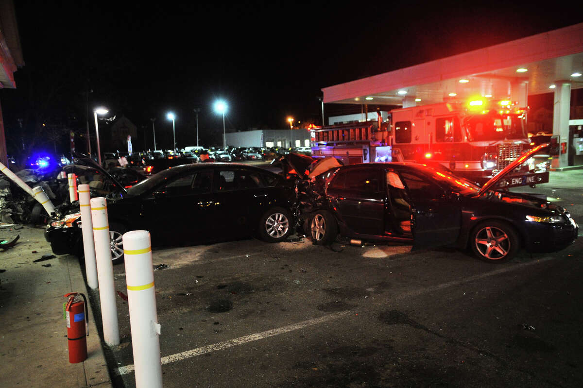 A Nissan Maxima is crushed against a safety pillar and a Redbox dvd rental machine after striking six cars at the Cumberland Farms gas station at 975 King's Highway East in Fairfield, Conn. on Monday, March 24, 2014. Police said the car crashed into the station, which is at the bottom of I-95 exit 24 southbound, at a high rate of speed after exiting the highway.