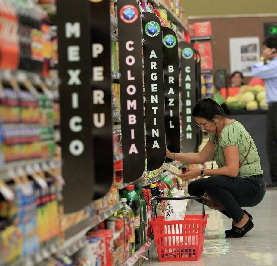 "A customer looks over an item in the ""Foods of the World"" aisle during the Fiesta Market Place's grand opening last summer. Photo: Karen Warren, Staff / © 2013 Houston Chronicle"