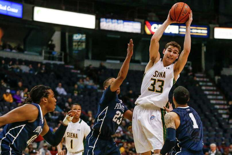 Siena's Rob Poole, 33, gets a pass off over Penn State defenders during the College Basketball Invit