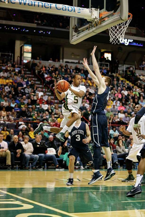 Siena's Evan Hymes, 5, makes a jumping pass around Penn State defenders during the College Basketball Invitational quarterfinal game at the Times Union Center, Monday, March 24, 2014 in Albany, N.Y.  Siena won over Penn State 54-52. (Dan Little/Special to the Times Union) Photo: Dan Little / Dan Little