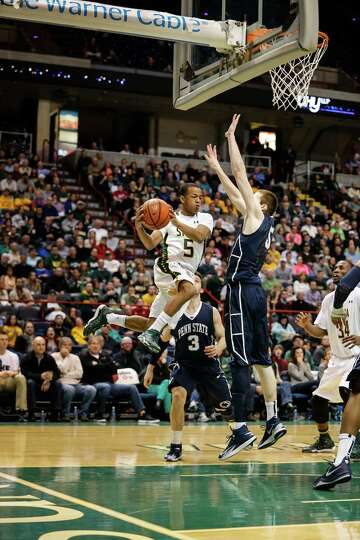 Siena's Evan Hymes, 5, makes a jumping pass around Penn State defenders during the College Basketbal