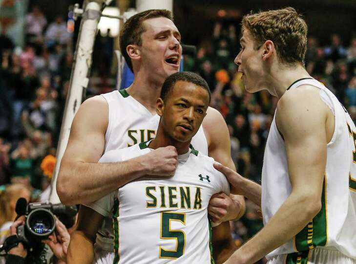 Siena's Brett Bisping, back, and Rob Poole, right, embrace Evan Hymes after making the game winning