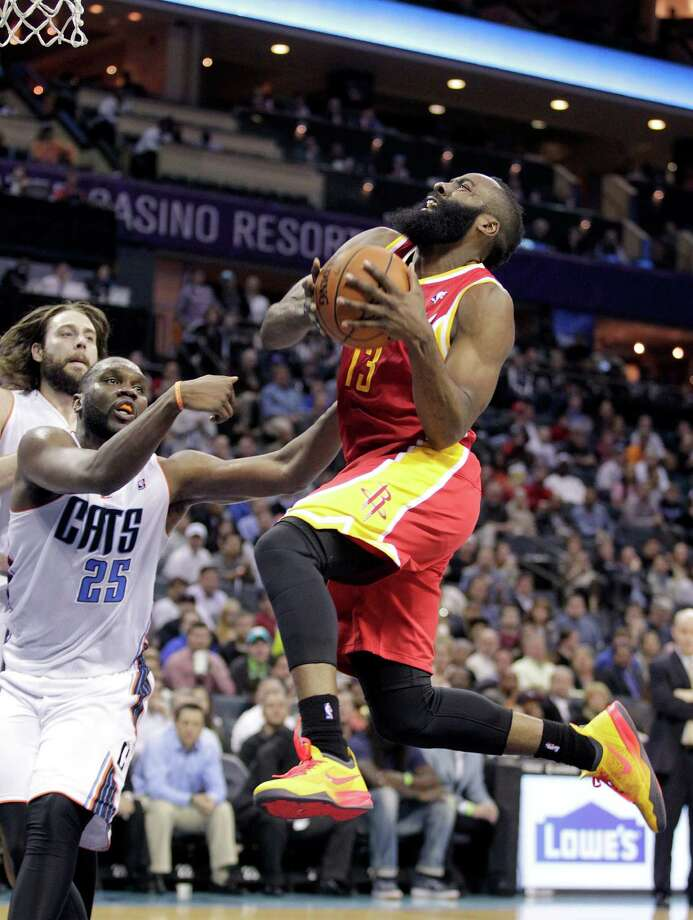 Rockets guard James Harden (13) tries to complete the play despite being fouled by the Bobcats' Al Jefferson (25) during the second half Monday night. Harden was 11-of-19 from the field for a game-high 31 points and added five assists. Photo: Bob Leverone, FRE / FR170480 AP