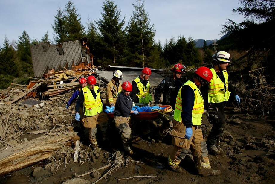 A search and rescue team brings out the tarp-covered body of a victim of Saturday's mudslide, Monday, March 24, 2014, near Oso, Wash. The search for survivors of the deadly mudslide grew Monday to include scores of people who were still unaccounted for as the death toll from the wall of trees, rocks and debris that swept through a rural community rose to at least 14. (AP Photo/seattlepi.com, Joshua Trujillo) Photo: Joshua Trujillo, Associated Press