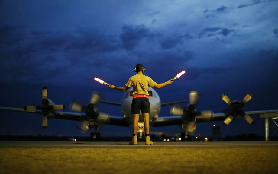 BULLSBROOK, AUSTRALIA - MARCH 24:  A ground controller guides a Royal Australian Air Force AP-3C Orion on the tarmac upon its return from a search for Malaysian Airlines flight MH370 over the Indian Ocean, at RAAF Base Pearce north of Perth, March 24, 2014 in Bullsbrook, Australia. Australian Prime Minister Tony Abbott told Parliament on Monday night that a Royal Australian Air Force P-3 Orion aircraft had located two new objects floating in the southern Indian Ocean on Monday.  (Photo by Jason Reed-pool/Getty Images) *** BESTPIX *** Photo: Pool, Getty Images