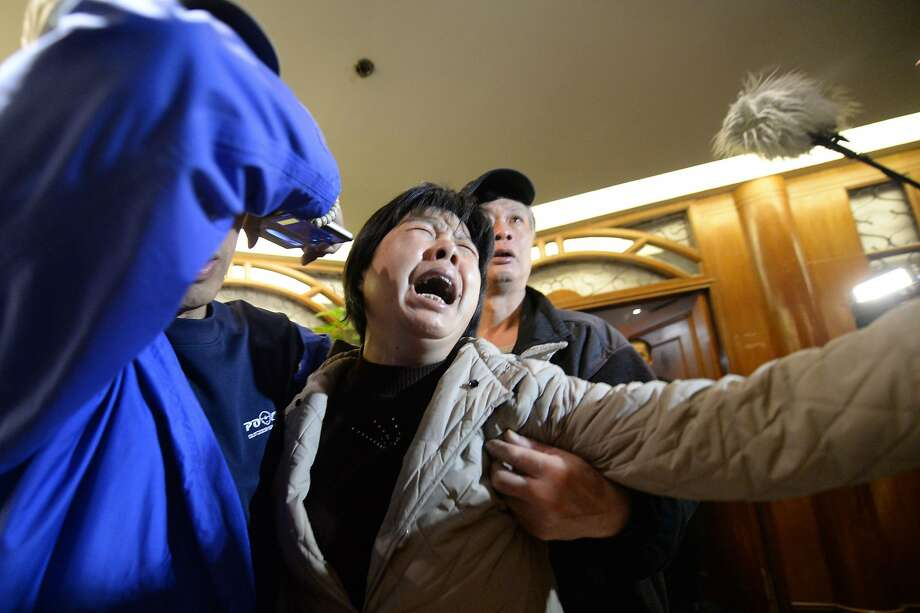 A relative (C) of passengers on Malaysia Airlines flight MH370 cries after hearing the news that the plane plunged into Indian Ocean at a hotel in Beijing on March 24, 2014.  The missing Malaysia Airlines jet came down in the Indian Ocean, Prime Minister Najib Razak said March 24, as the airline reportedly told relatives it had been lost and that none on board survived. AFP PHOTO / GOH CHAI HINGOH CHAI HIN/AFP/Getty Images Photo: Goh Chai Hin, AFP/Getty Images