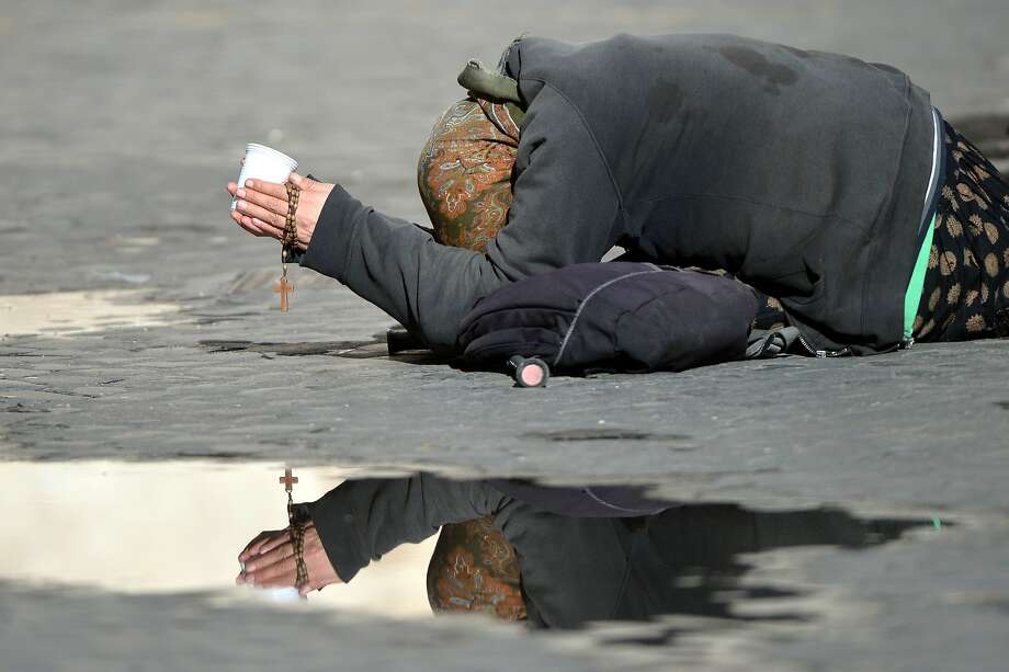 TOPSHOTS A beggar lies on the ground asking for some money, while holding a rosary, in a street of Rome on March 24, 2014. AFP PHOTO / GABRIEL BOUYSGABRIEL BOUYS/AFP/Getty Images Photo: Gabriel Bouys, AFP/Getty Images