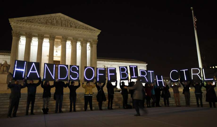 "A group of people organized by the NYC Light Brigade and the women's rights group UltraViolet, use letters in lights to spell out their opinion, in front of the Supreme Court, Monday, March 24, 2014, in Washington. Holding the ""H"" in ""Hands"" is Rep. Keith Ellison, D-Minn. The Supreme Court is weighing whether corporations have religious rights that exempt them from part of the new health care law that requires coverage of birth control for employees at no extra charge. (AP Photo/Alex Brandon) Photo: Alex Brandon, Associated Press"