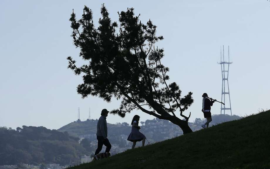 Tim Walker, left, walks up a hill with his nieces and his dog Sugar at Alta Plaza Park with Sutro Tower, an antenna tower located atop Twin Peaks, shown at rear in San Francisco, Monday, March 24, 2014. (AP Photo/Jeff Chiu) Photo: Jeff Chiu, Associated Press