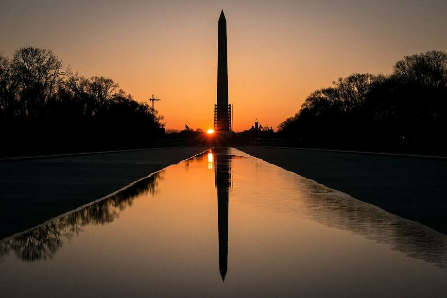 The sun peeks through the scaffolding around the Washington Monument at dawn in Washington, Monday, March 24, 2014. The National Park Service has announced they will reopen the earthquake damaged structure in May. (AP Photo/J. David Ake) Photo: J. David Ake, Associated Press