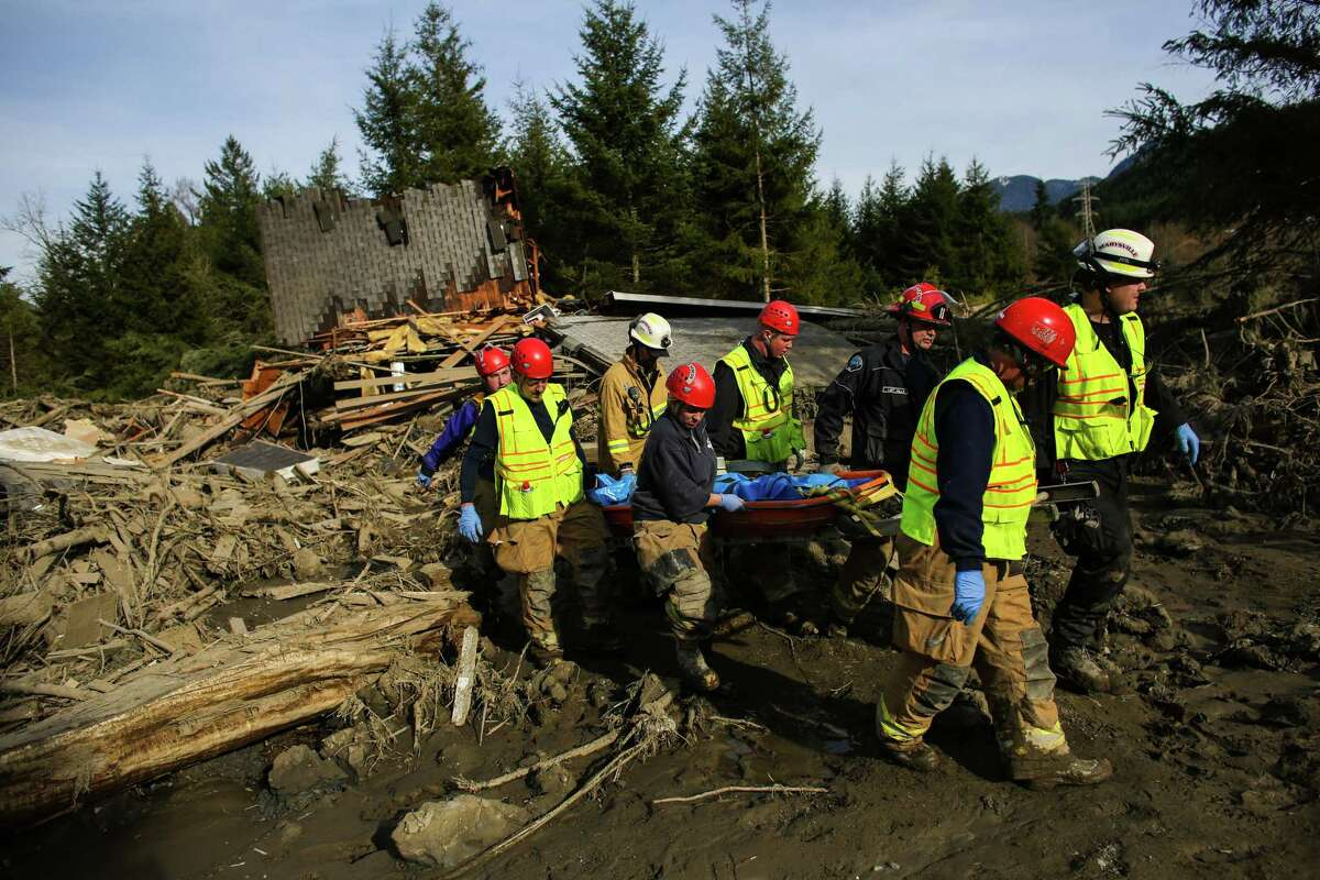 Rescue workers remove a body from the wreckage.
