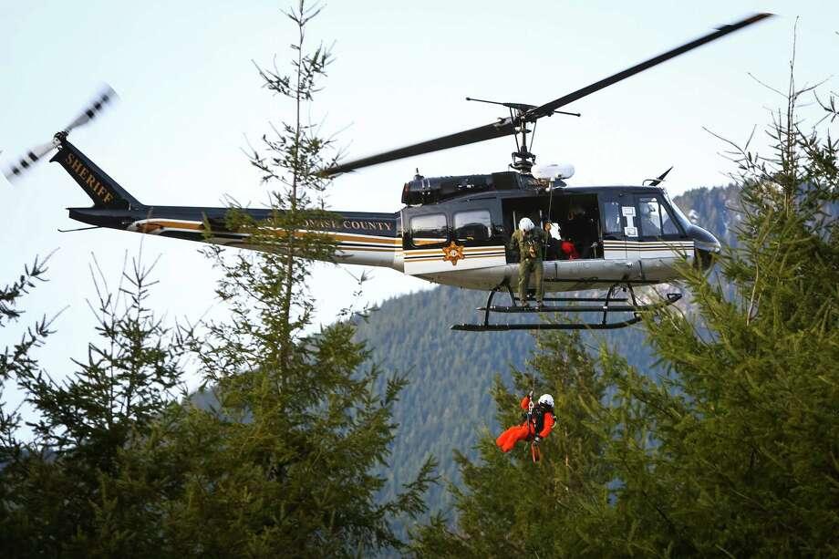 A rescue worker is lowered into the debris field. Photo: JOSHUA TRUJILLO, SEATTLEPI.COM / SEATTLEPI.COM